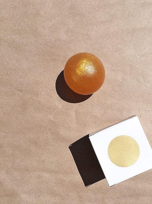 琥珀色の球体石鹸と四角いパッケージ