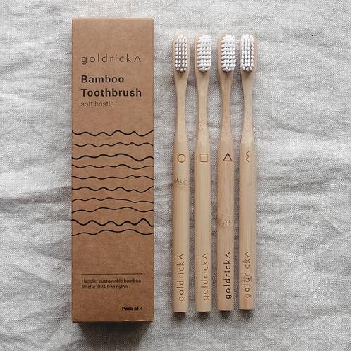 並べられた4本の孟宗竹製歯ブラシと、波線があしらわれた紙製のパッケージ