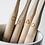 コップに入れられた、柄に四角、波線、三角、丸のシンボルが刻印された4本の竹製歯ブラシ