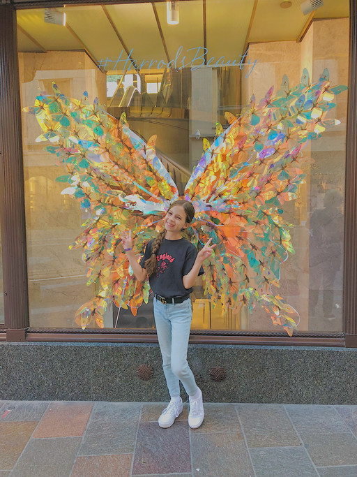 Ashley posing with wings in front of Harrods in London, England