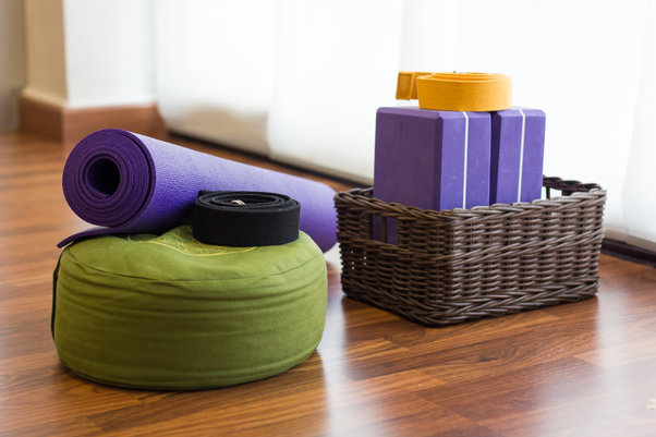 Various yoga props on studio wood floor.