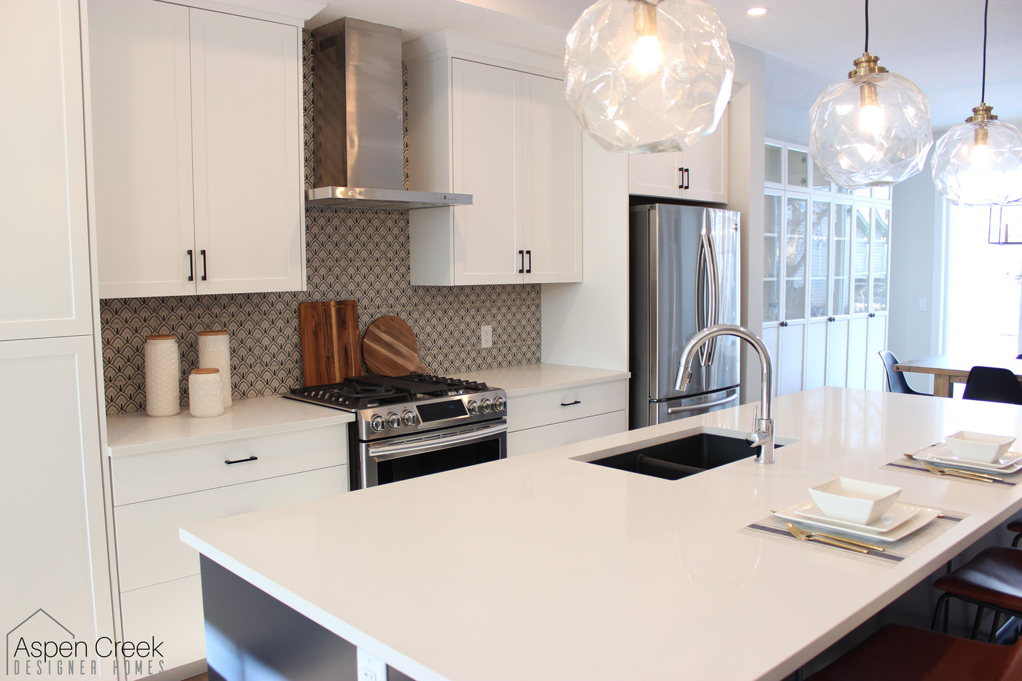 Light and bright kitchen interior design. With bold backsplash patterned cement tile that creates a focal point. The clean white island is perfect for family gatherings.