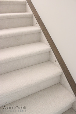 Perfectly coordinated staircase carpet with neutral wood trim pieces that match the hardwood.