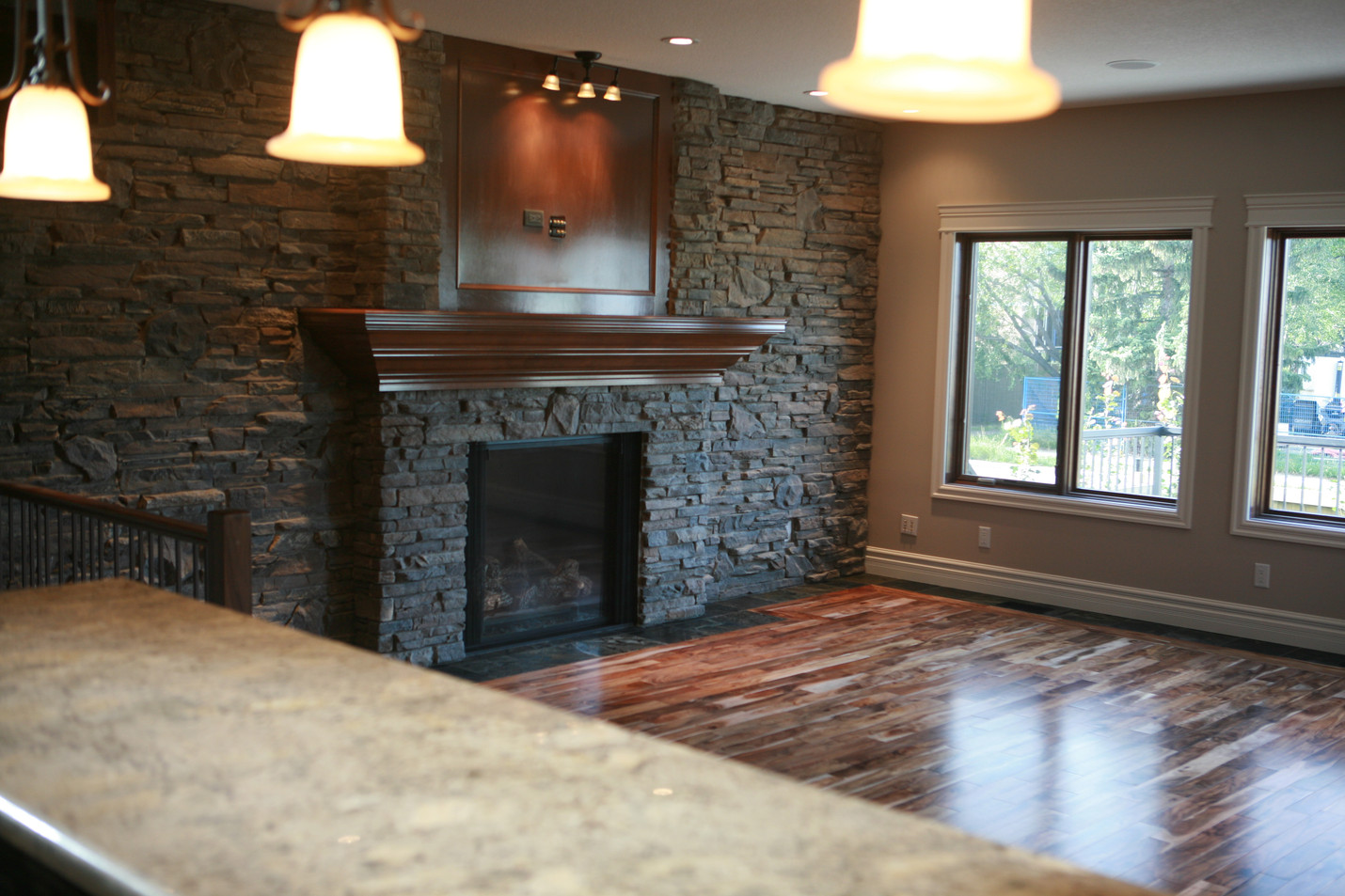 Ledgestone tile for this fireplace in this main floor living room lets the beauty in the hardwood stand out.
