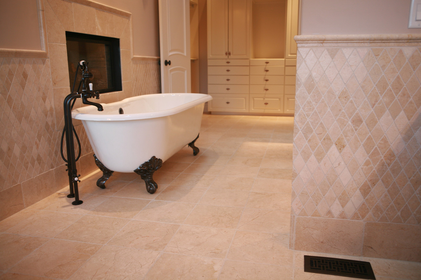 This natural stone bathroom tile is a perfect addition to this master ensuite bathroom. The clawfoot tub and fireplace makes this the perfect retreat.