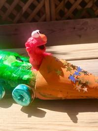 Elmo in his recycled bottle car.jpg