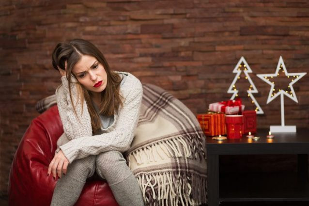 Woman on a red chair feeling sad at Christmas