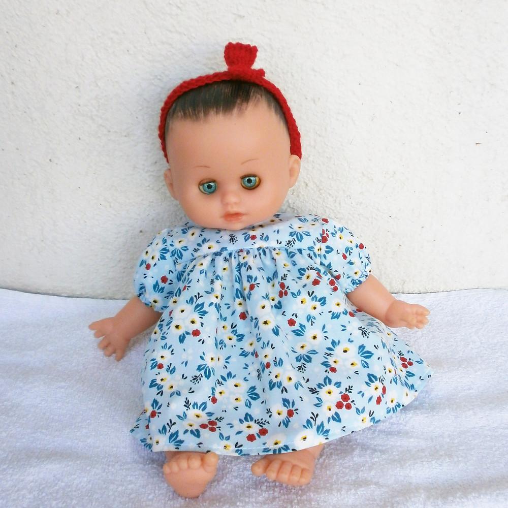 Pour poupon Petit Câlin de Petitcollin, une robe bleue à fleurs