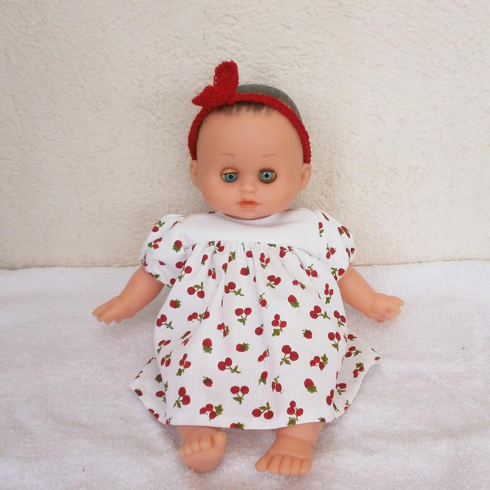 Pour poupon Petit Câlin de Petitcollin, une robe imprimée de petits fruits rouges