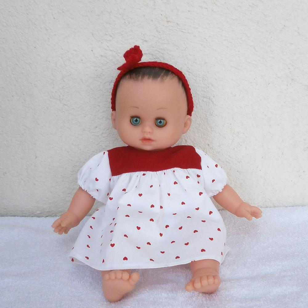 Pour poupon Petit Câlin de Petitcollin, une robe petits coeurs rouges