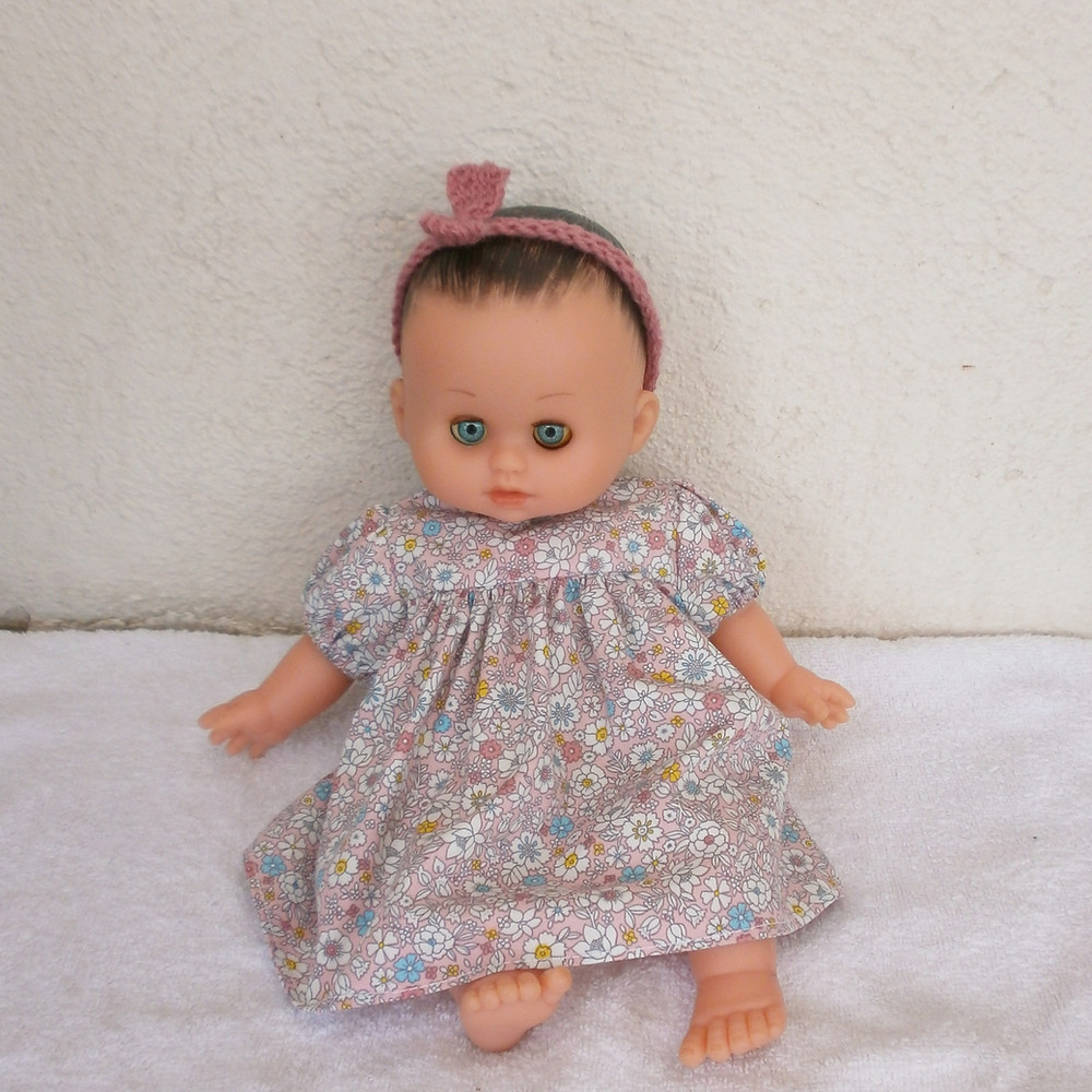 Pour poupon Petit Câlin de Petitcollin, une robe rose à fleurs