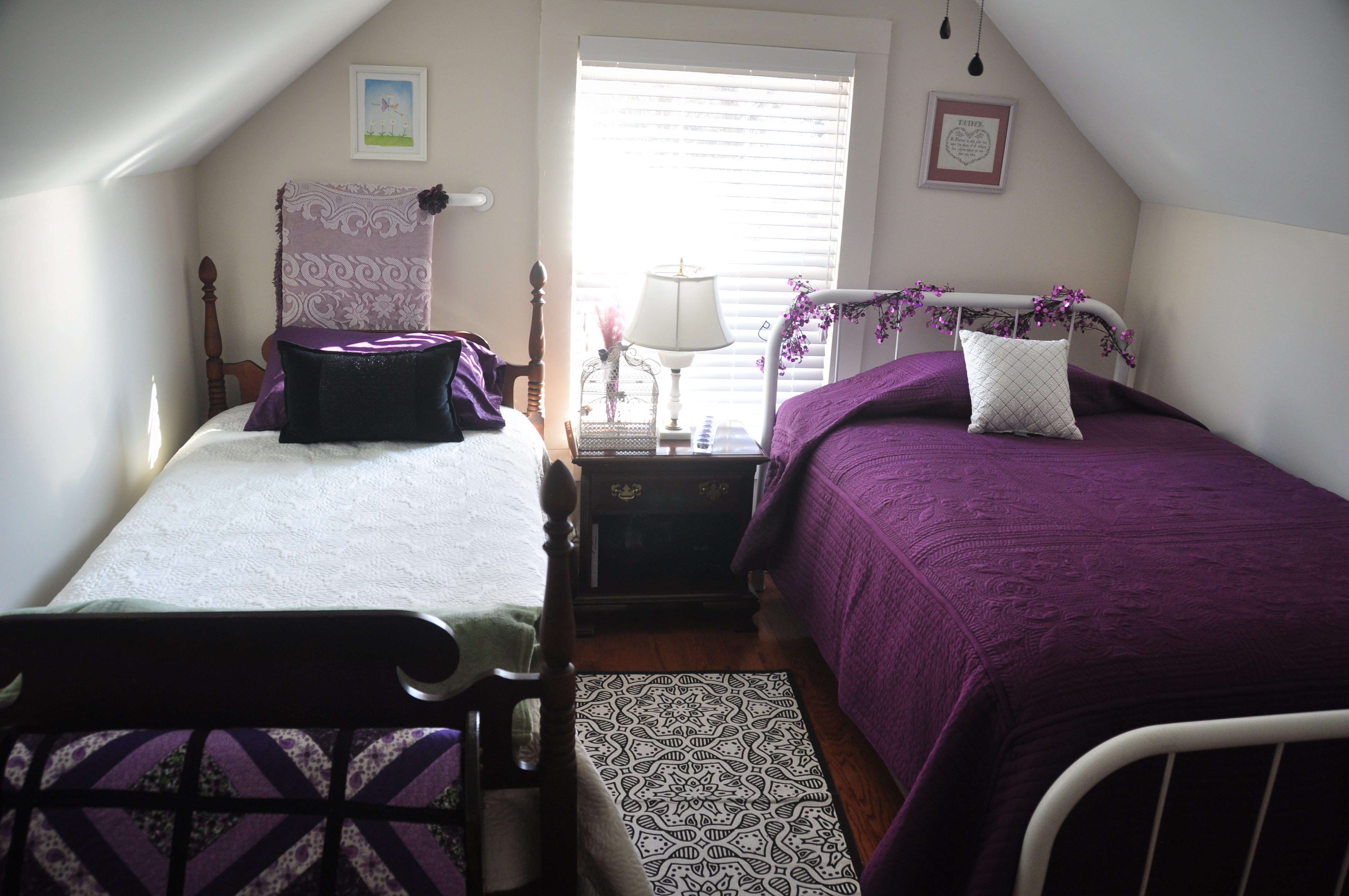 Two beds with purple linens
