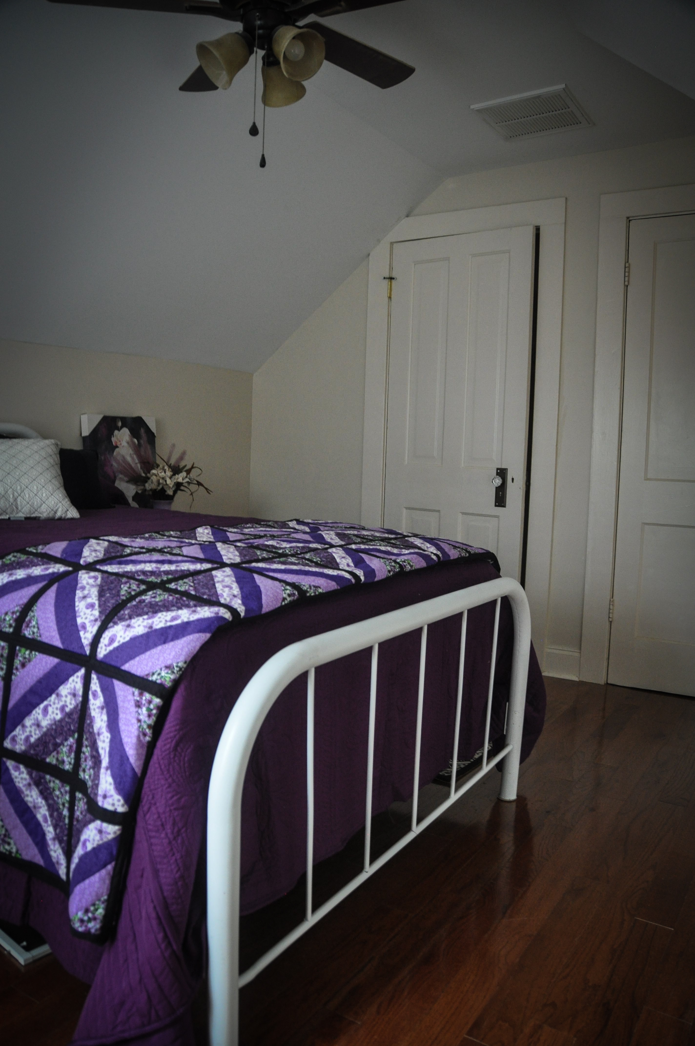 Twin bed with white frame and purple