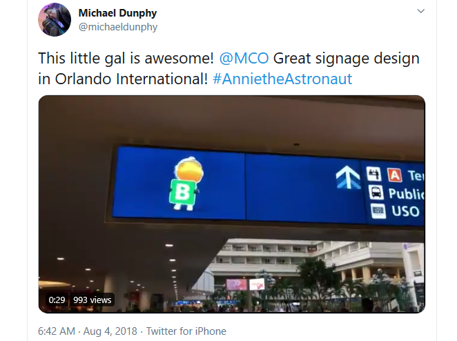 """A Twitter screenshot showing a passenger calling Orlando International Airport's signage design """"awesome"""" with a picture of an animated astronaut on a digital wayfinding sign"""