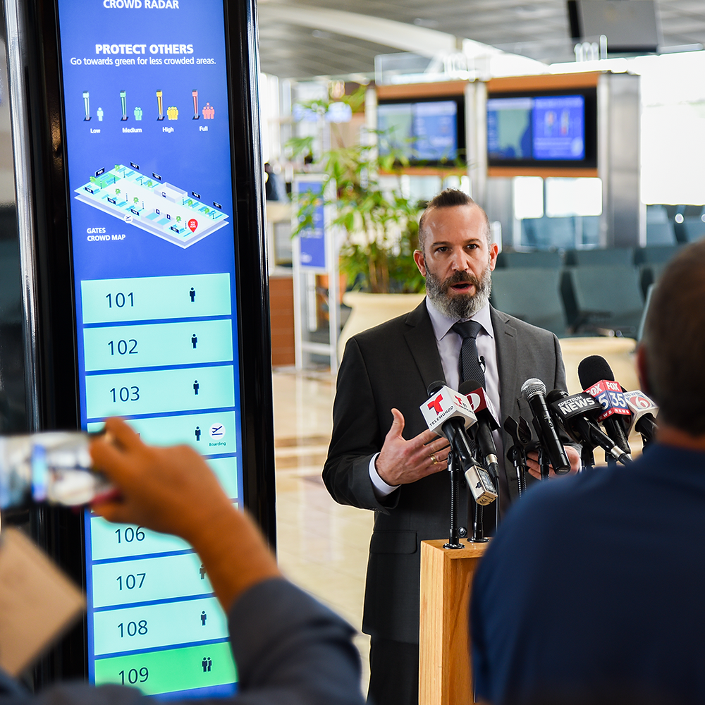 Synect CEO Yahav Ran speaks in front of a ReadySeeGo digital signage totem