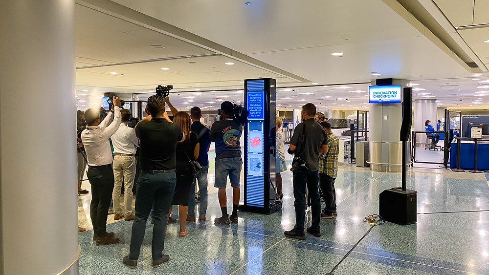Airport digital signage totem at the TSA's Innovation Checkpoint surrounded by news media and camera people