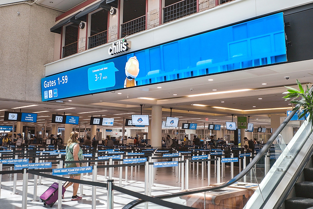 An LED video wall showing an animated astronaut and airport security wait times