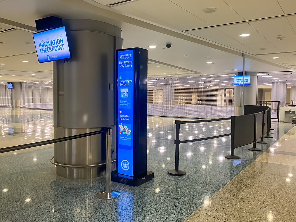 A digital signage totem at LAS security checkpoint showing screening-related content