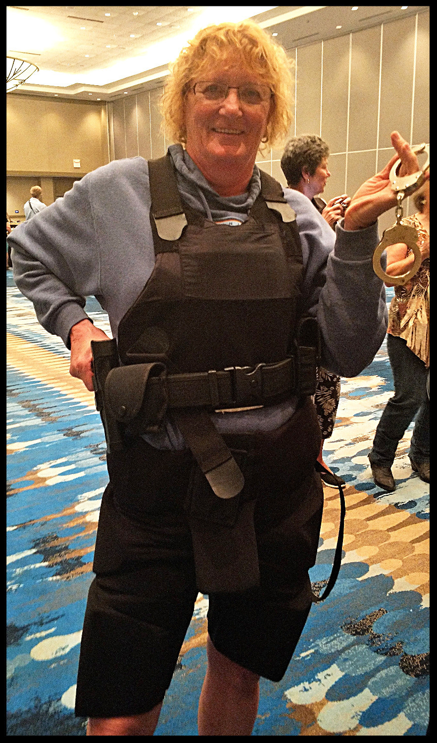 "Wearing a vest, utility belt, and pants. Holding the ""gun"" and cufflinks. The object was to sit in a chair as if you needed to use the bathroom. Very heavy and cumbersome. We all agreed this would be a pain for female officers who are not allowed to take them off while using the facilities."