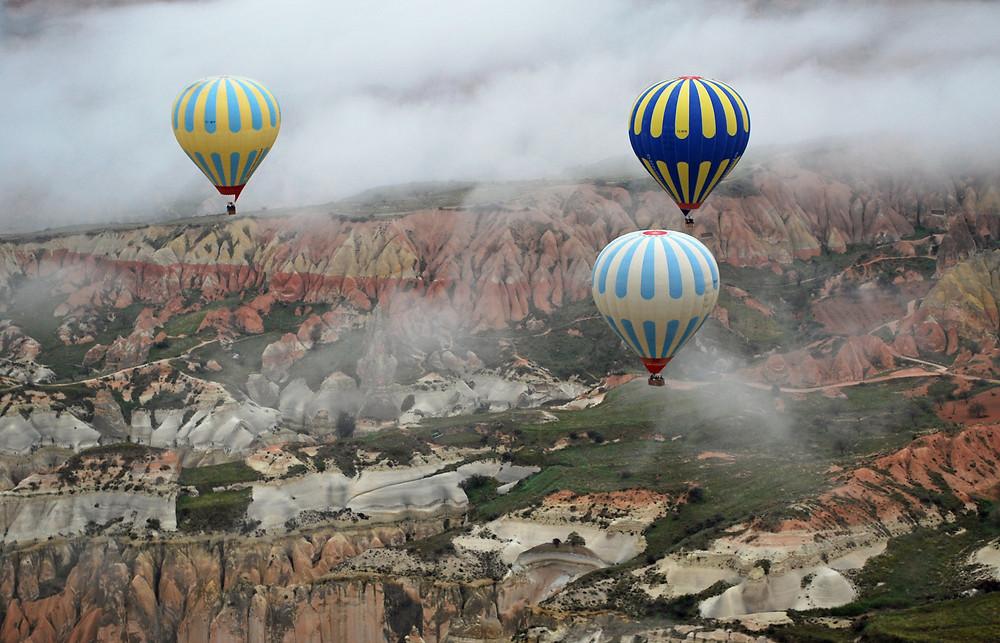 Hot air balloons floating above Cappadocia