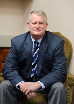Our owner Kevin Payne wearing a dark blue suit with blue striped tie.