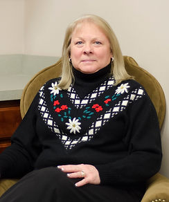 Our Accounting & Auditing Manager Cheri wearing a black sweater with an embroidered flower pattern.