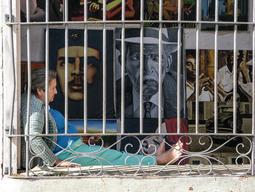 Cuba-woman-sitting-in-art-shop-window _J