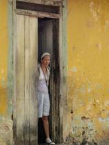 Cuba-woman-standing-in-doorway-yellow-ho