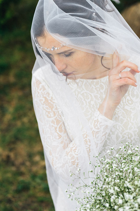 Прекрасная невеста в роскошном свадебном платье, сидящая на диванчике.