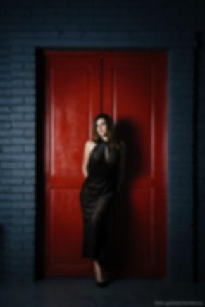 Венец элегантности в центре композиции. Темно - коричневое платье на фоне ярко - красной двери элегантно подчеркивает хорошую фигуру модели.