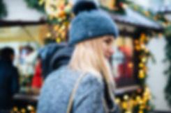 Светловолосая дама в элегантной зимней одежде на фоне светящихся гирлянд рождественских палаток.