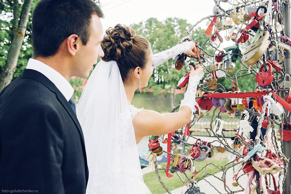 Навешивание замочка на стилизованное дерево или мост становится традиционным элементом современной свадьбы.