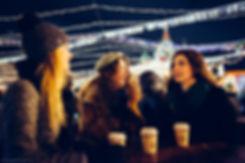 Теплый свет прожекторов и согревающий кофе в руках окружают друзей уютом.