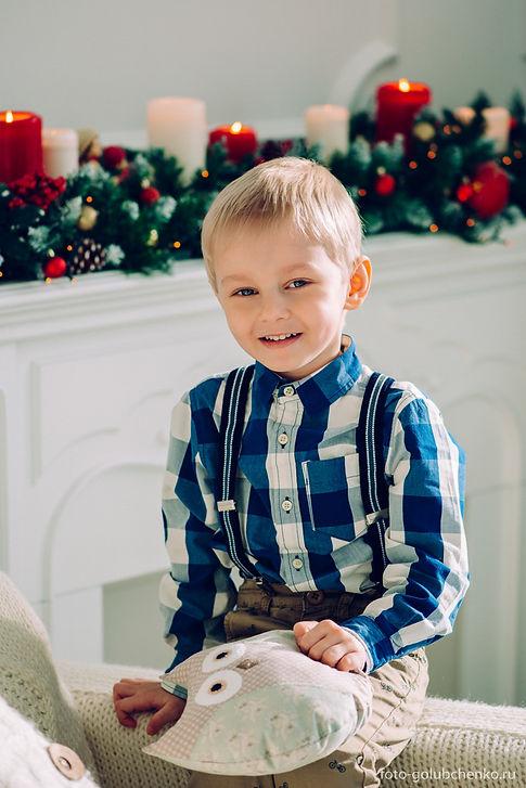 Веселый малыш на кресле в стильной одежде с подушкой - совой на руках.
