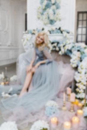 Светловолосая дева нежится в ослепительной красоте своего утреннего наряда.  Оформление комнаты свечами и цветами добавляет романтичности и сказочности предсвадебному настроению.