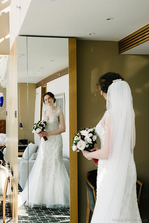Невеста держит в руках букет, который гармонично сочетается с платьем.