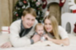 Семейная фотосессия вместе с малышом. Счастливая семья смотрит в объектив фотокамеры.