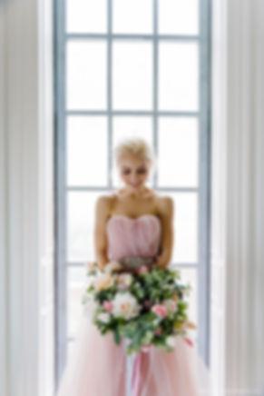 Невеста с цветами стоит у окна. Гармоничное сочетание цвета букета и платья создает ощущение хорошо подготовленной свадьбы.