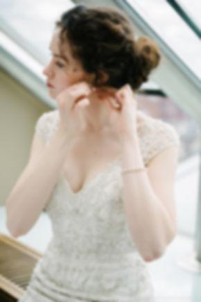 Красивый портрет девушки, вставляющей сережку в ухо.