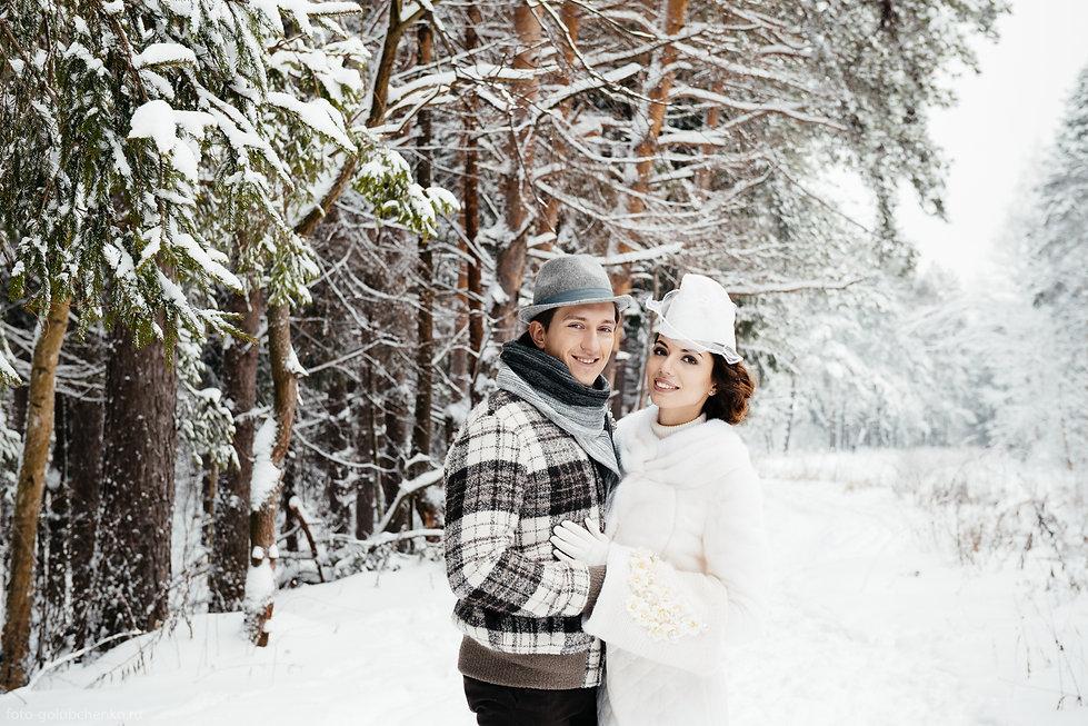 Молодожены на фотосессии в зимнем парке.  Одежда хорошо гармонирует с окружающей природой.