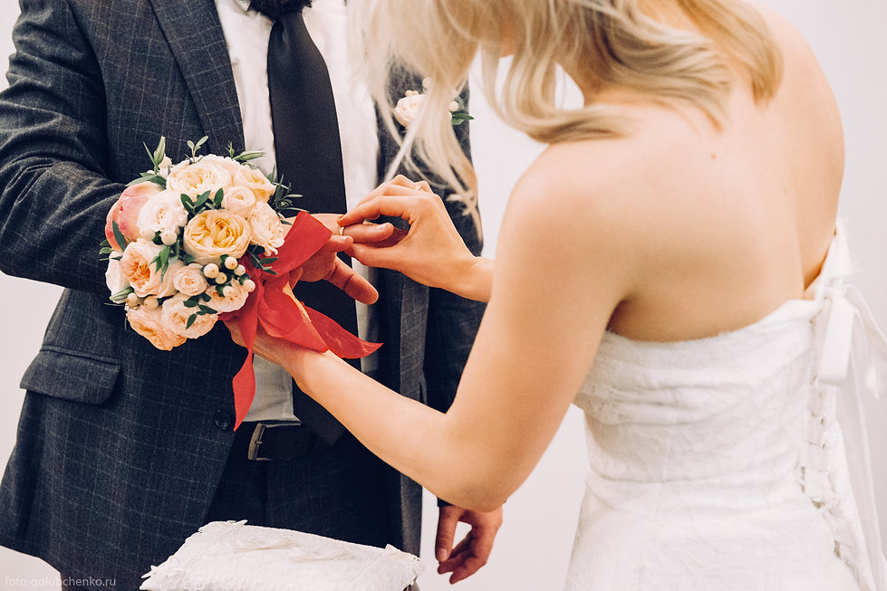 Нежные руки невесты оккуратно надевают кольцо на палец своему будущему мужу.  Элегантный свадебный букет придает торжественному моменту ощущение праздника.