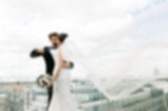 Молодая пара позирует облокотившись на стеклянное ограждение веранды. Развивающаяся фата заполняет большую часть кадра, добавляя хаоса и детализации.