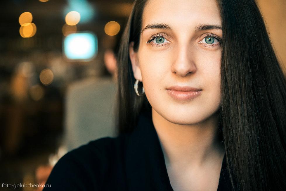Светлые пятна осветительных приборов кафе на заднем плане композиционно поддерживают блеск глаз девушки, делая фотографию более привлекательной.