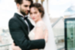 Stylish looking bride and groom posing on the background of the urban landscape