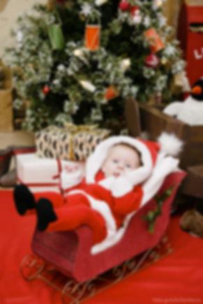Младенец в костюме санта – клауса в санях – кадр умиляющий его родителей.