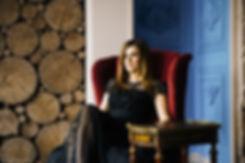 Смелые контрастные темные цвета интерьера подчеркивают элегантный и грациозный вид девушки сидящей в кресле.