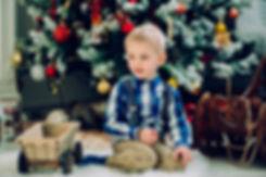 Фотосъемка детей в новогоднем интерьере. Наряд, по цвету контрастный к окружающим предметам, гармонично сочетается с ними и при этом ребенок отчетливо выделяется в центре композиции.