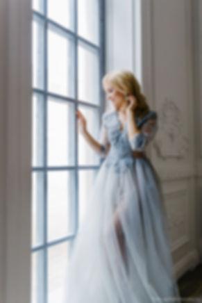 Невеста стоит в платье лавандового цвета у окна. На ее лице отражена застенчивая радость и ожидание предстоящей праздничной церемонии.
