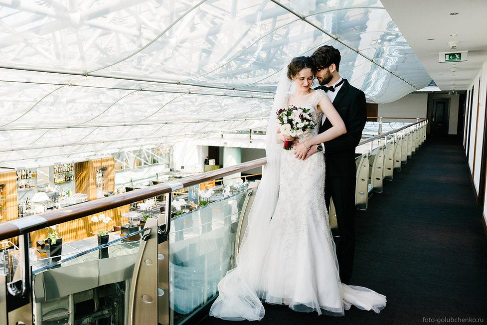 Пара позирует в коридоре дорогого отеля.