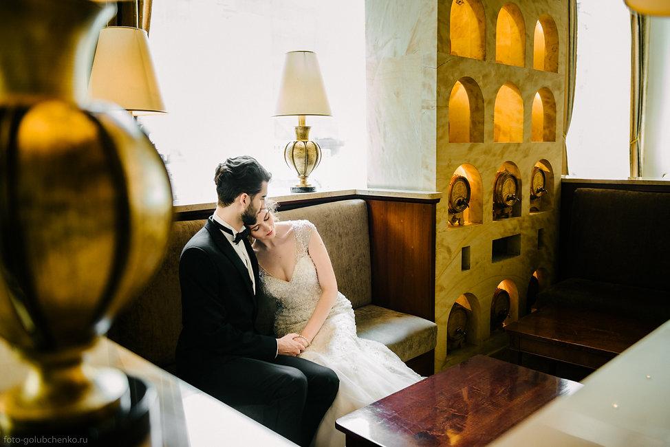 Молодая девушка положила голову на плечо своему суженному. Красивый интерьер украшает фотографию.